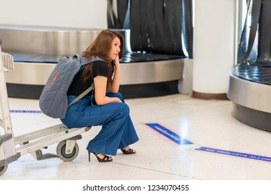 Woman feeling exhausted sitting on airport trolley, waiting for luggage at the airport. Concept of airline travelers troubles when baggage not arriving at destination with the flight.