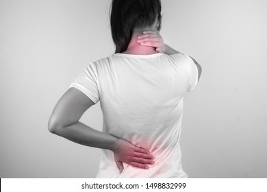 A woman feeling exhausted and suffering from neck and back pain and injury on white background. Health care and medical concept.