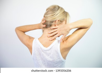 A woman feeling pain in her neck.