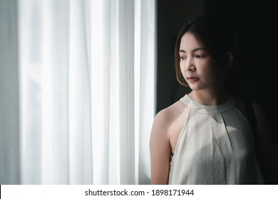 woman feeling sad standing alone near the window and looking outside. unhappy, sadness, negative emotion concept.