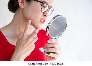 Woman feeling serious when she saw the problem of acne and scar inflamed on her skin by the mini mirror. Conceptual shot of Acne and Problem Skin on female face.