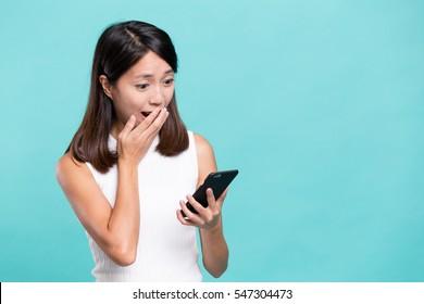 Woman feeling shock reading on mobile phone
