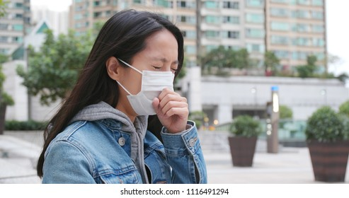 Woman feeling sick, cough and sneeze with wearing face protective mask