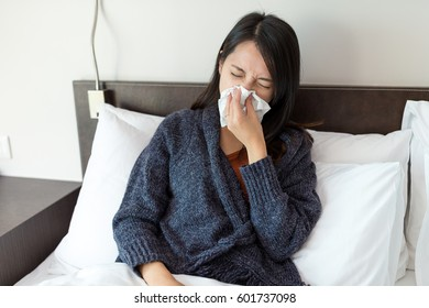 Woman feeling sick and lying on bed