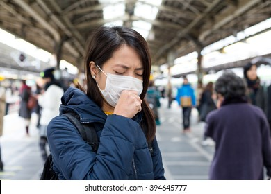 Woman feeling sick and wearing face mask in metro station platform