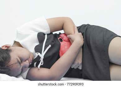 Woman feeling stomach cramps feeling very unwell holding hot water bottle In bed.Conception Abdominal pain, menstrual cramps