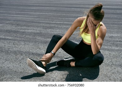 Woman Feeling Tired After Running Outdoors. Sad Exhausted Disappointed Female Athlete In Sportswear Sitting On Ground After Losing Sports Competition, Feeling Pain In Injured Leg. High Resolution.