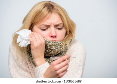 Woman feels badly. How to bring fever down. Fever symptoms and causes. Sick girl with fever. Girl sick hold thermometer and tissue. Measure temperature. Break fever remedies. Seasonal flu concept.