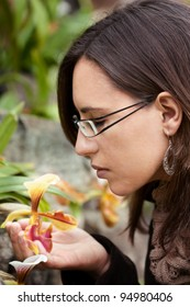 Woman feels the smell of a yellow orchid flower in Spring