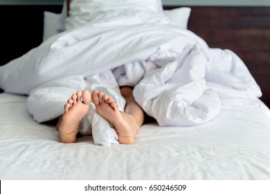 Woman feet in bed , Two feet in bed cover with white blanket , woman feet who sleeps in her bed closeup , Woman relaxing in bed