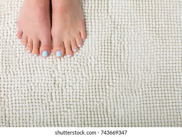 Woman feet with a blue pedicure standing on a white bathroom rug