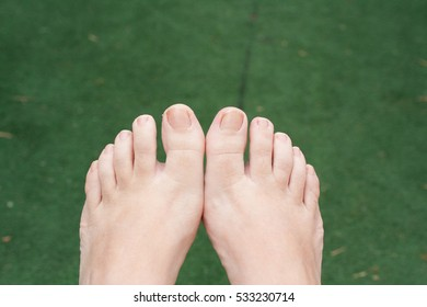 Woman feet and fingers seen from above with green grass below