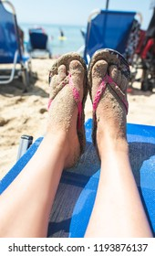 Woman feet with flip flops on the beach. Sunbeds and umbrellas on background