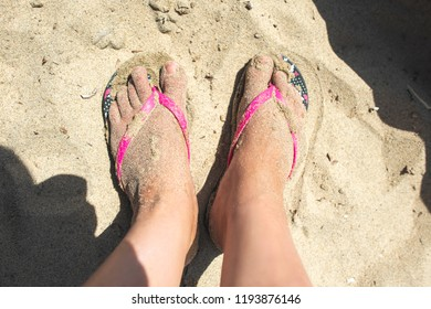 Woman feet with flip flops on the sand. Sunny day