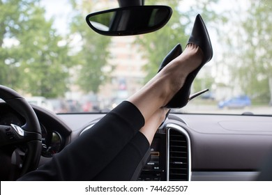 Woman feet heels on car dashboard car interior