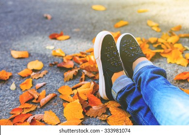Woman feet with jeans and black shoes surrounded by golden leaves. Vintage effect.