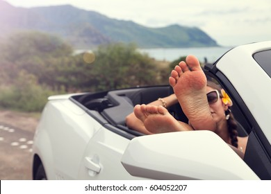 Woman with feet up in luxury convertible, relaxing after walking. Hawaii, USA.