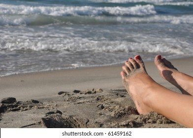 woman feet lying and relaxing on the beach