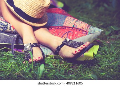 woman feet on grass in flat summer sandals lean on pillows  hat lay on legs