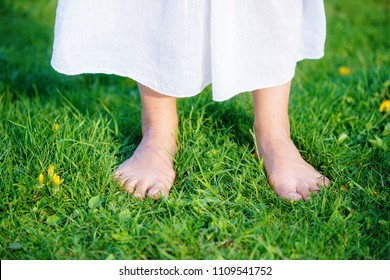 woman feet on the grass with white cloth.