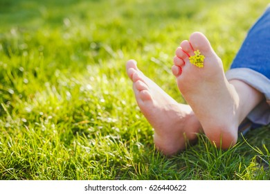 Woman feet on the green grass in the morning