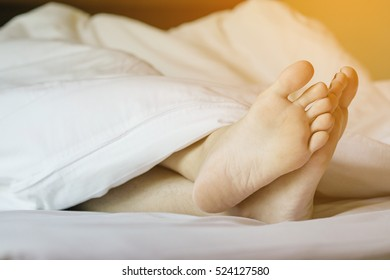 Woman feet on white bed