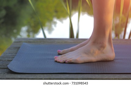 Woman feet on yoga mat before practicing on pond