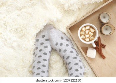 Woman feet in polka dot socks and cup of hot chocolate with marshmallow on creamy shaggy blanket. Top view point.