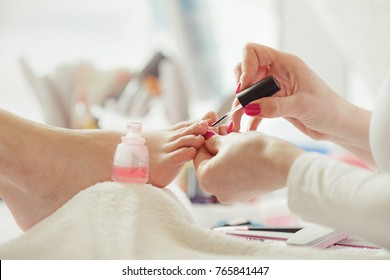 Woman feet receiving pedicure. Close up concept.