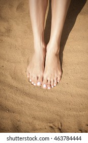 Woman feet with red toenails on sand