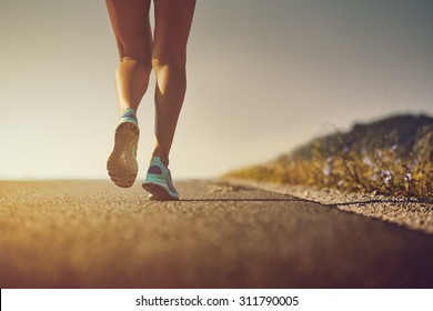 Woman feet in running shoes going for a run on the road at sunrise or sunset. Shallow depth of field, low angle, toned with warm instagram like filter, flare effect.