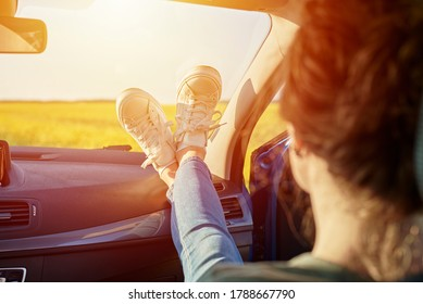 Woman feet in sneakers on a car dashboard. Roadtrip and freedom travel concept