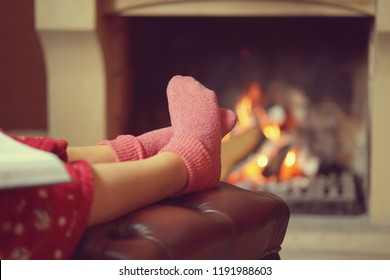 Woman feet with socks sitting near fireplace with a warmth background. Woman in warm socks resting near fireplace at home with book. Toning.