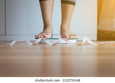 Woman feet standing on weigh scales with tape measure in foreground,Weight loss,Body and healthcare concept