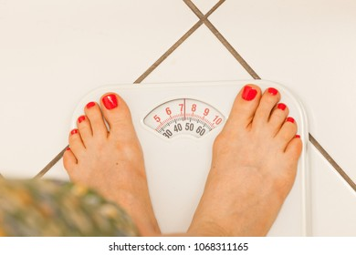 Woman feet standing on weight machine weighing scale showing results of dieting.