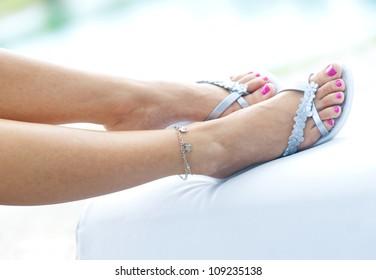 woman feet in summer flip flop sandals