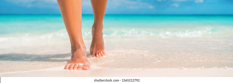 Woman feet walking on caribbean beach barefoot closeup of foot coming out of water after swim banner panorama. Honeymoon travel vacation,