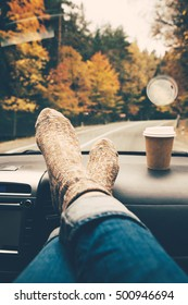 Woman feet in warm socks on car dashboard. Drinking take away coffee on road. Fall trip. Rain drops on windshield. Freedom travel concept. Autumn weekend.