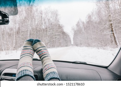 Woman feet in warm woolen socks on car dashboard over snow view. Having weekend trip in winter forest. Freedom travel concept.