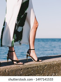 Woman feet wearing fashionable high heels summer shoes. Female walking on seaside pier next to sea water.