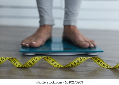 Woman feets on the scales. Yellow measure tape in focus. Diet idea.