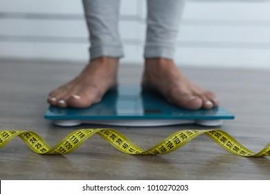 Frauen füttern auf der Waage. Gelbes Messband im Fokus. Diätgedanke.