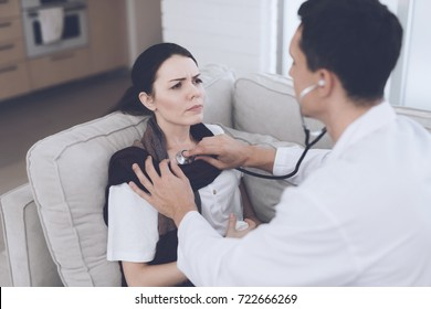 The woman fell ill and called the doctor at home. She sits on the sofa with a blanket. Doctor in a white coat listens to her with a stethoscope