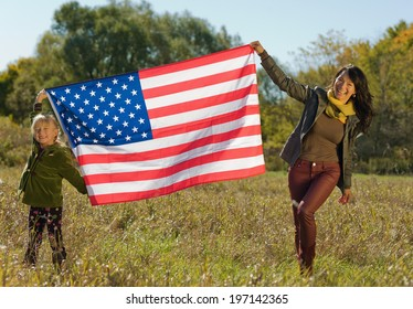 A woman and a female child holding up an American flag in a field.