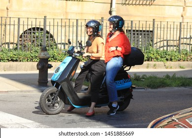 a woman and a female pillion rides along Marcy ave  in the bedford Stuyvesant section of Brooklyn on a sunny summer afternoon in Brooklyn NY july 15 2019