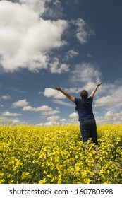 Woman in a field of canola lifts her arms in joy
