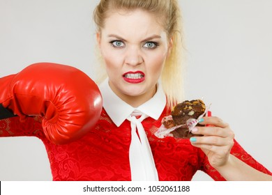 Woman fighting with her bad habits, being on diet. Female wearing boxing glove holding sweet dessert, chocolate cupcake.