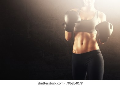 Woman in fighting position with strong abs and body