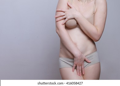A woman with a figure after giving birth. Stretch marks on the belly. Close the body with his hands. Oppression and shame