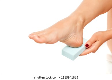 woman file her feet with a pumice stone on white background